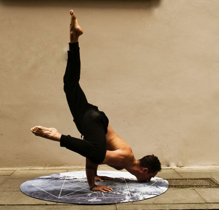 Man on a circular yoga mat doing an arm balance