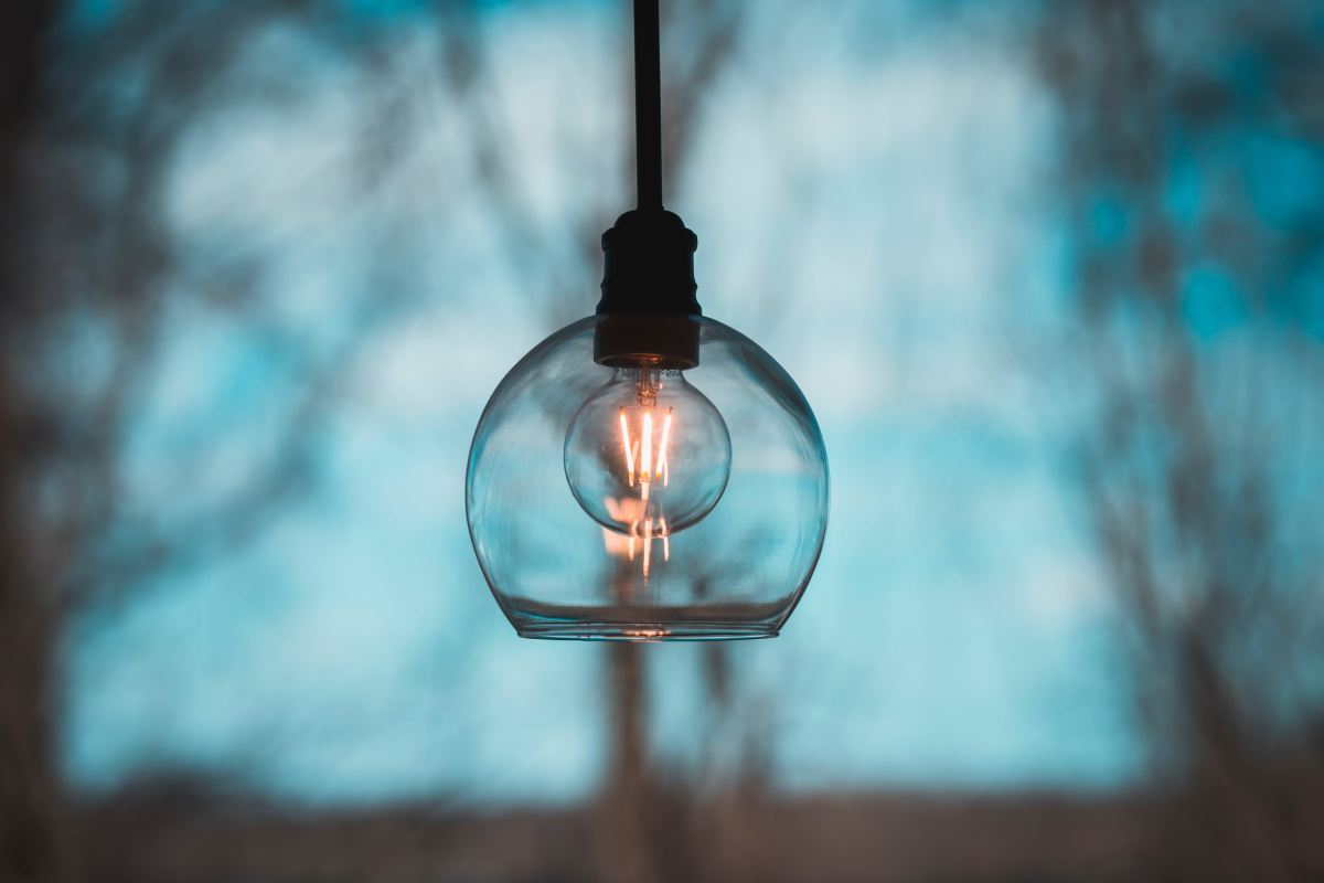 A simple lightbulb in a glass shade hanging against a background of a window overlooking trees and sky