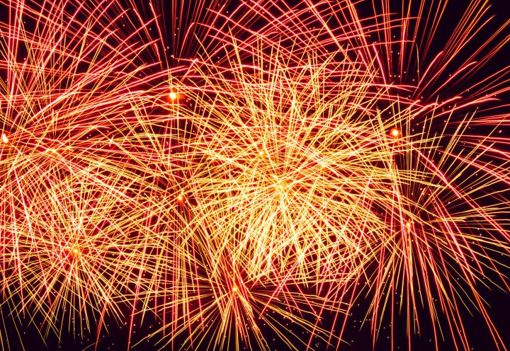 Fireworks - bright yellow, orange and red against a black sky