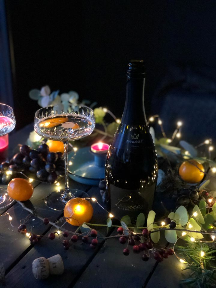 Bottle of Prosecco and champagne blow glass set in a display of fruit and lights
