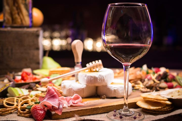 Wine glass (red) next to cheese and board and nibbles